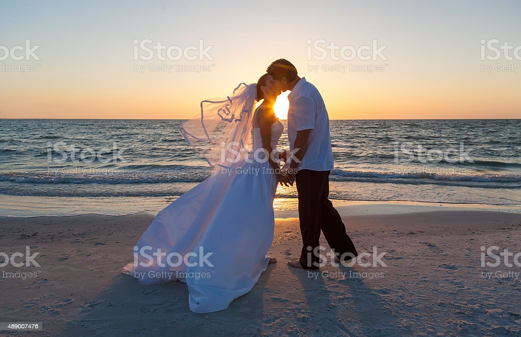 Bride and Groom Married Couple Sunset Beach Wedding stock photo