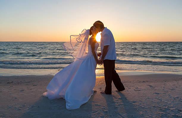 Novia y el novio casado par atardecer boda en la playa - foto de stock