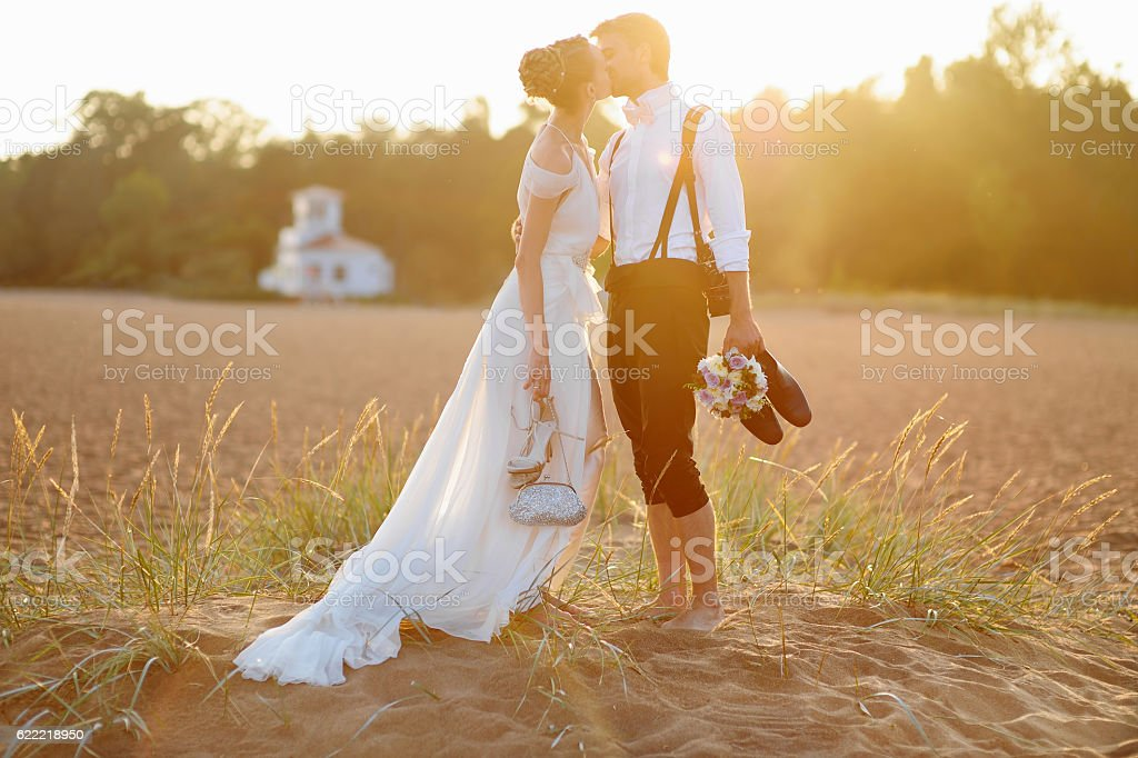 Bride and groom on a beach at sunset stock photo