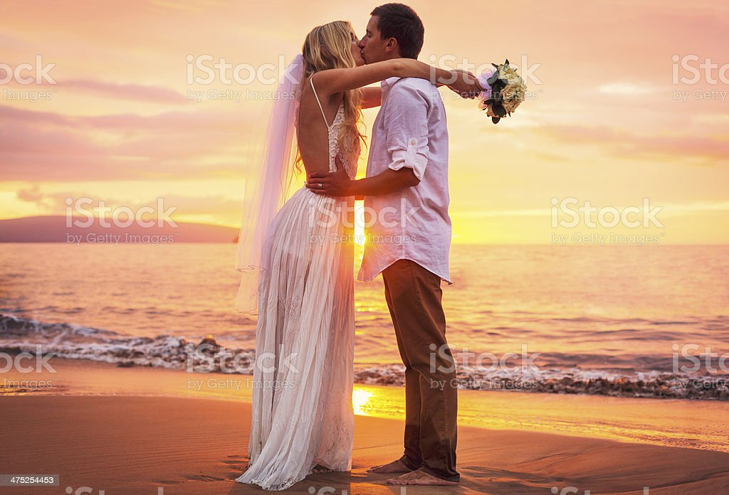 bride and groom on beach at sunset stock photo