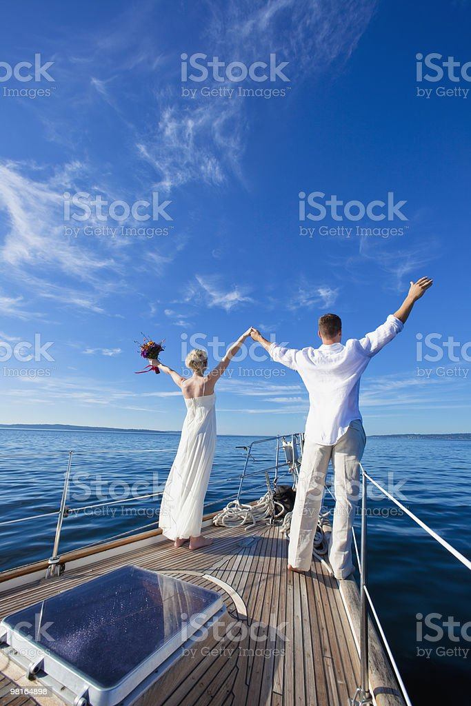 Bride and groom on sailboat looking out, arms up royalty-free stock photo