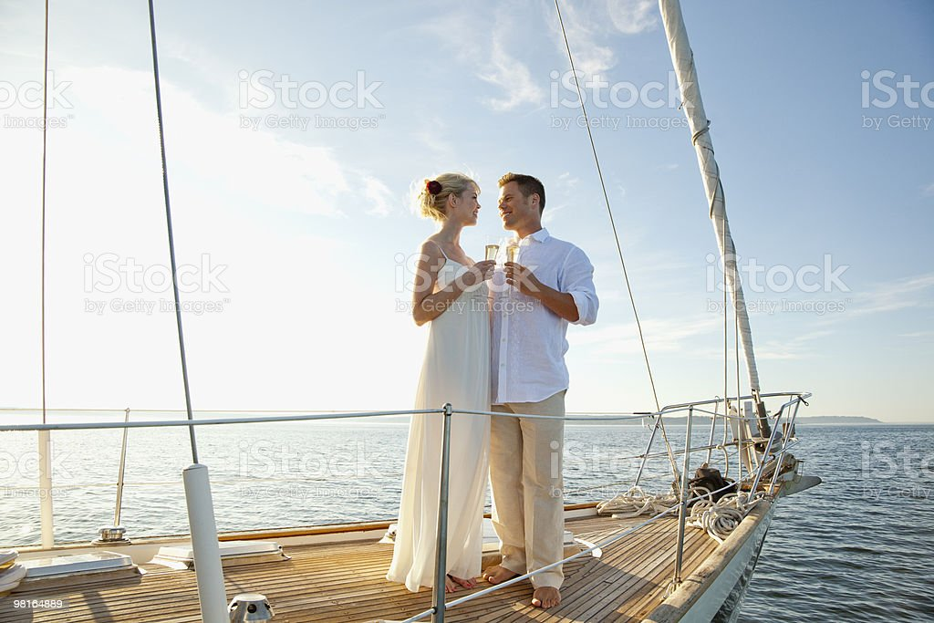 Bride and groom on sailboat toasting champagne royalty-free stock photo
