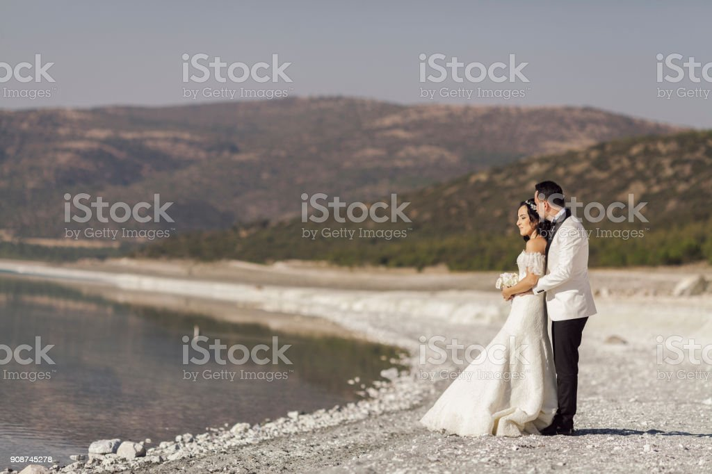 Bride and groom on the beah posing for camera stock photo