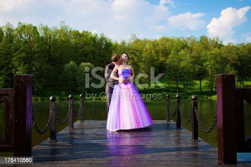 674214372istockphoto Bride and groom on the bridge 175410580