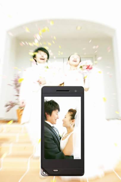 braut und bräutigam auf dem handy-display - hochzeitskleider online stock-fotos und bilder