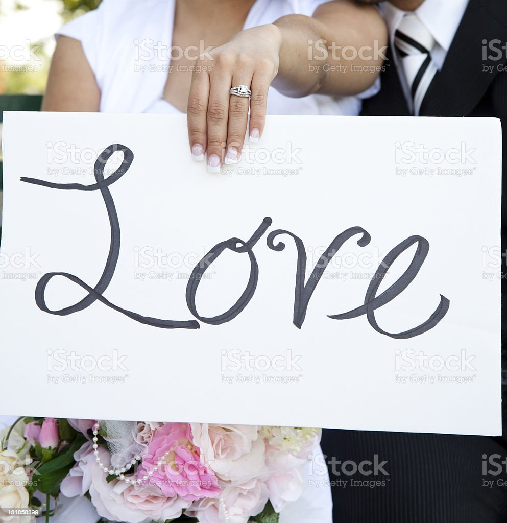 Bride and Groom outside with sign reading LOVE royalty-free stock photo
