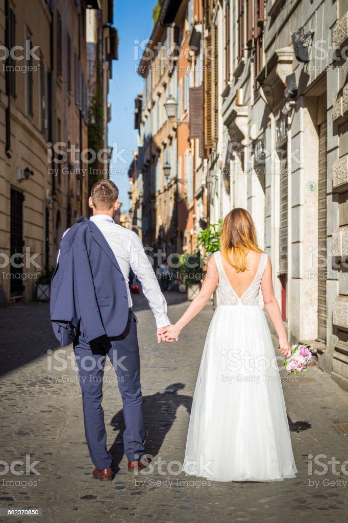 Bruden och brudgummen poserar på de gamla gatorna i Rom, Italien royaltyfri bildbanksbilder
