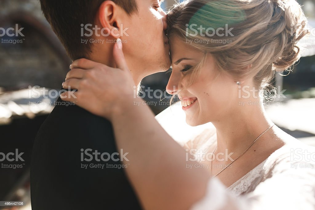 bride and groom posing on the streets stock photo