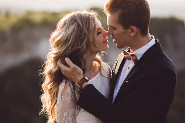 Bride and groom pretty portrait outdoors in the mountains. Fantastic view at background stock photo