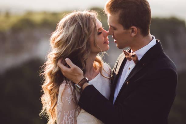 braut und bräutigam ziemlich porträt draußen in den bergen. fantastische aussicht im hintergrund - verlobungskleider stock-fotos und bilder