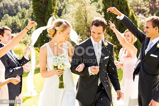 Happy couple walking while guests throwing confetti on them during wedding ceremony. Horizontal shot.