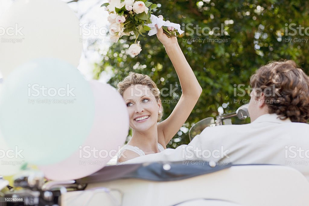 Bride and groom riding in convertible stock photo