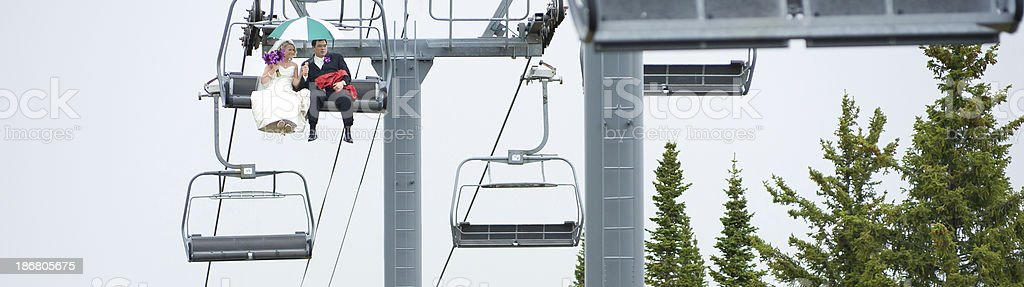 Bride and Groom Riding Up Chairlift Panorama stock photo