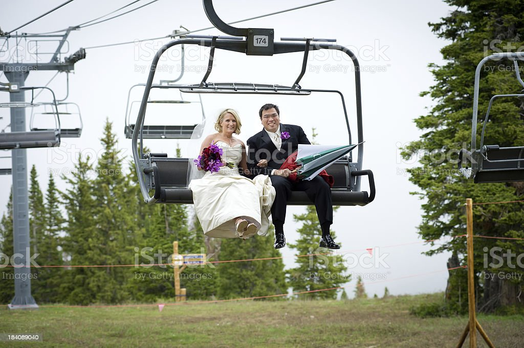 Bride and Groom Riding Up Chairlift stock photo