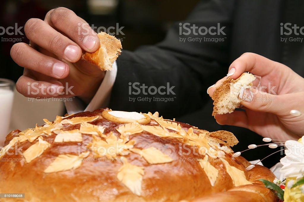 bride and groom salt broken piece of wedding loaf stock photo