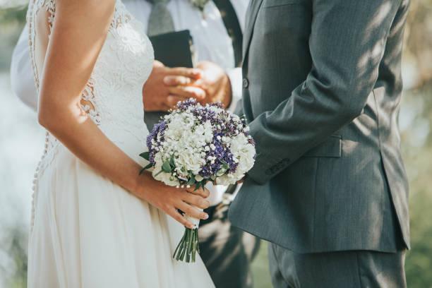 noiva e noivo dizendo votos durante a cerimônia de casamento ao ar livre - casamento - fotografias e filmes do acervo