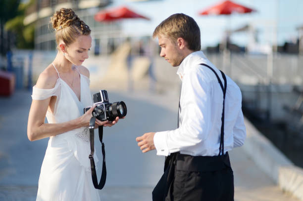 bride and groom shooting with an old camera - wedding photography and videography stock-fotos und bilder
