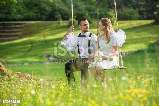 Bride and groom looking at each other while sitting on swing in park.