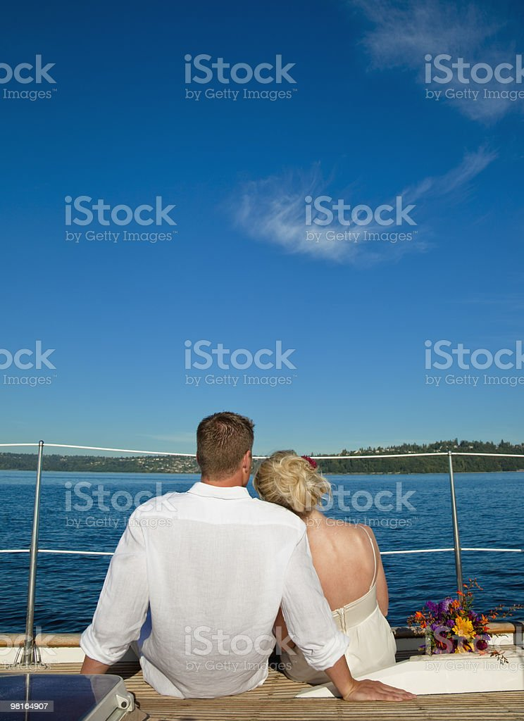 Bride and groom sitting on edge of sailboat foto stock royalty-free