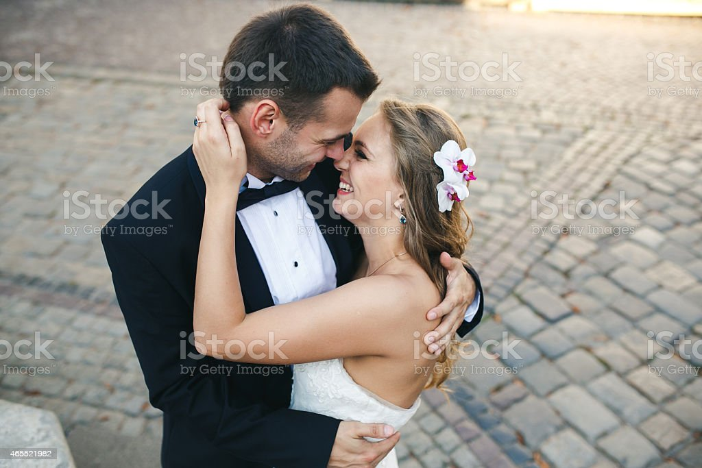 Bride and groom smiling and kissing on a stone street stock photo