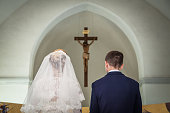 Photo taken during the wedding ceremony in Catholic church. Groom and bride stand before crucifix. Focus is on the crucifix. Newlyweds are in focus. Bride dressed in wedding dress and bridal veil. Groom dressed in suit and shirt. Photo taken from the back of bride and groom.