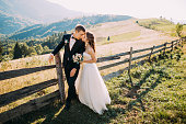 Bride and groom standing together near wooden fence on the road background