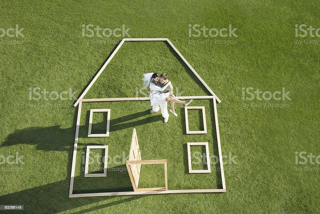 Braut und Bräutigam stehen auf Haus Kontur – Foto