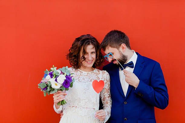 Bride and groom standing next to a red wall stock photo