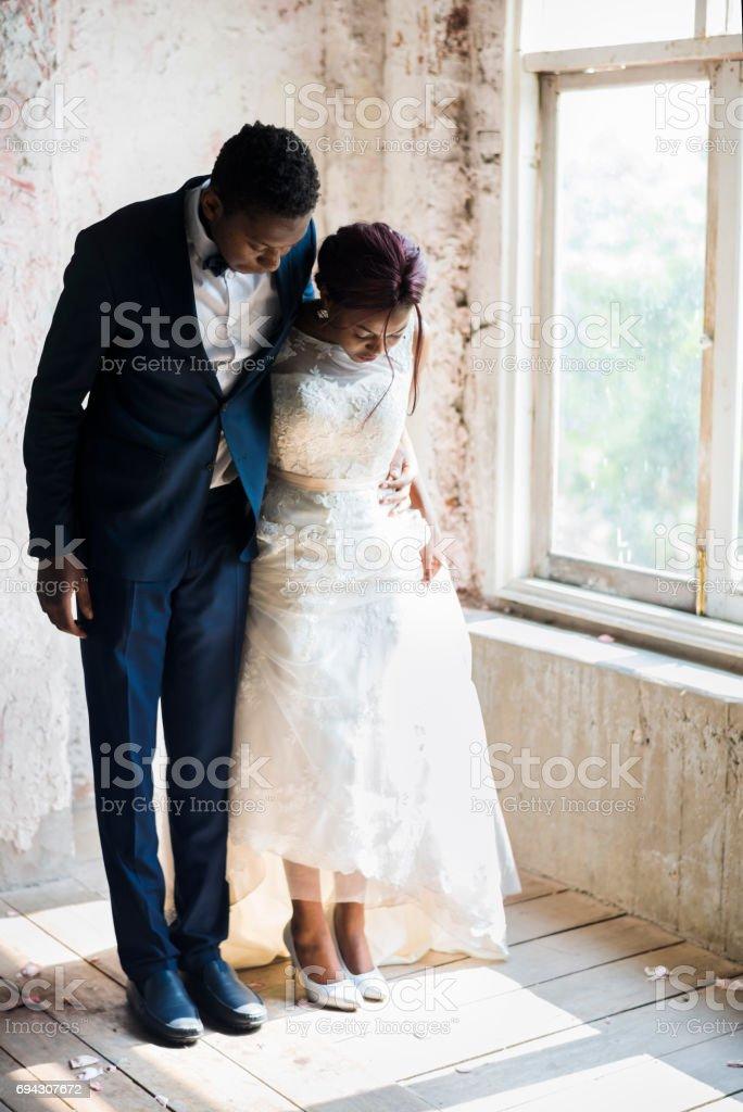 Bride and Groom Standing on Wooden Floor stock photo