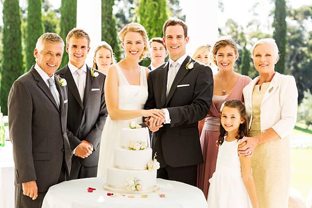 braut und bräutigam stehen mit gästen und schneiden hochzeitstorte - bräutigam tisch stock-fotos und bilder