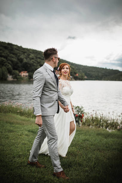 braut und bräutigam bei einem spaziergang am see - hochzeitsfrisur boho stock-fotos und bilder
