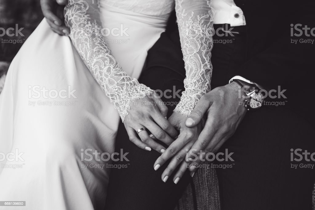 Bride and groom tenderly hold each other's hands. BW tone stock photo