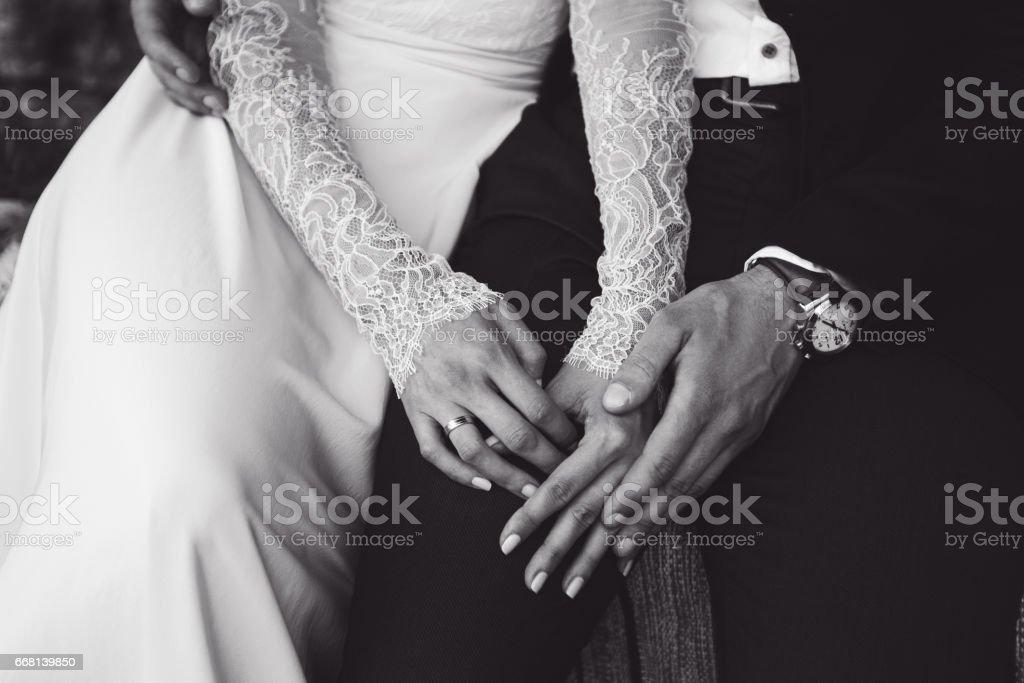 Noiva e noivo com ternura as mãos uns dos outros. Tom de BW - foto de acervo