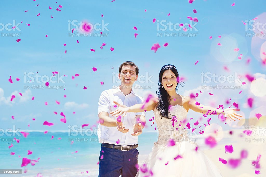 Bride and groom throwing petels on the beach stock photo