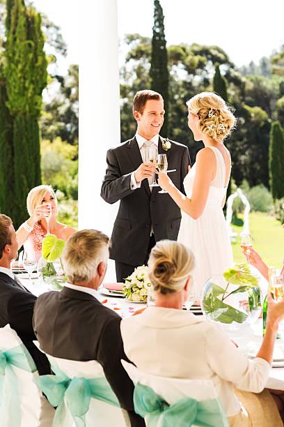 brautpaar anstoßen mit champagner flöten während der - bräutigam tisch stock-fotos und bilder
