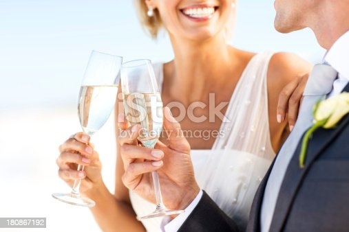 Midsection close-up of bride and groom clinking glasses with a champagne toast on beach. Horizontal shot.