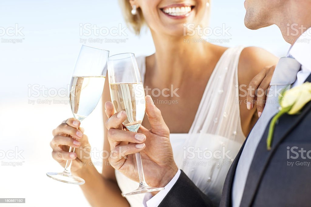 Bride And Groom Toasting Champagne Flutes On Beach stock photo