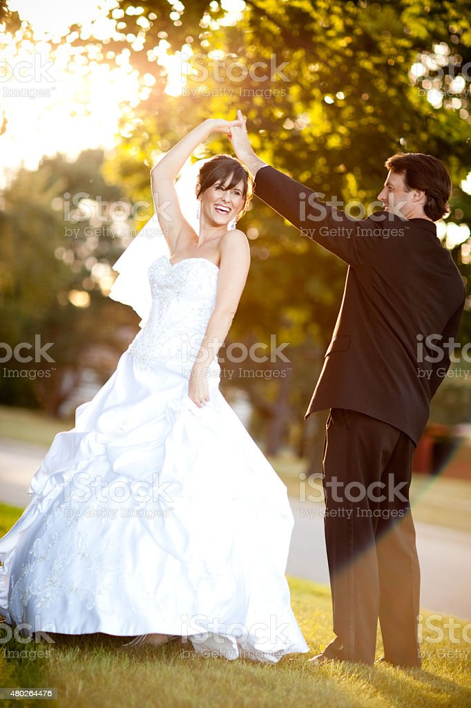 Bride and Groom Twirling and Dancing Together Outside stock photo