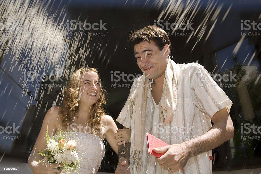 Bride and groom under heavy rain royalty-free stock photo