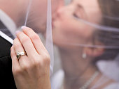 A close up of a bride's wedding ring as the couple kisses in the background.