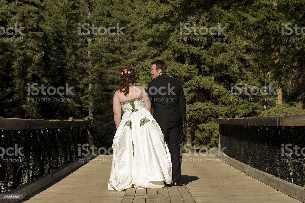 Bride and Groom Walking Across Bridge royalty-free stock photo