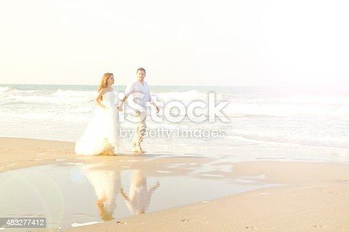 istock Bride and groom walking at beach 483277412