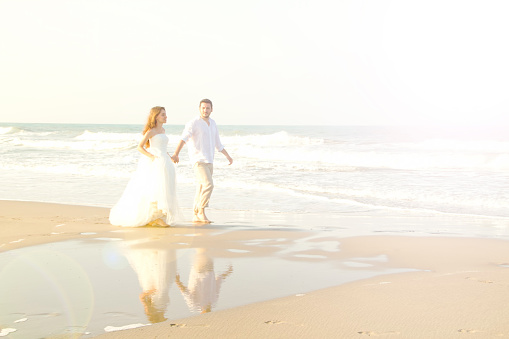 istock Bride and groom walking at beach 483277412