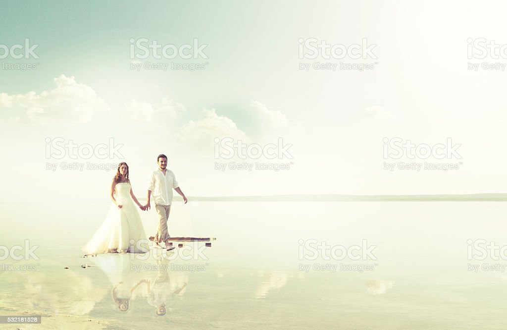 Bride and groom walking at beach stock photo
