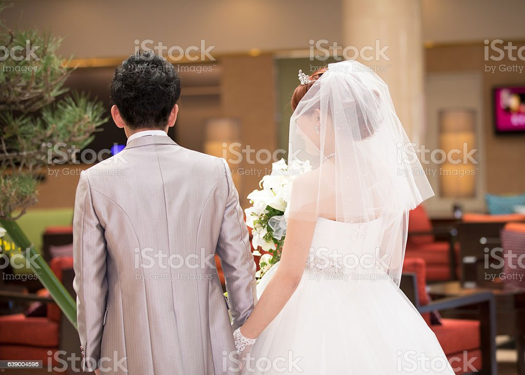 Bride and groom walking in hotel lobby stock photo