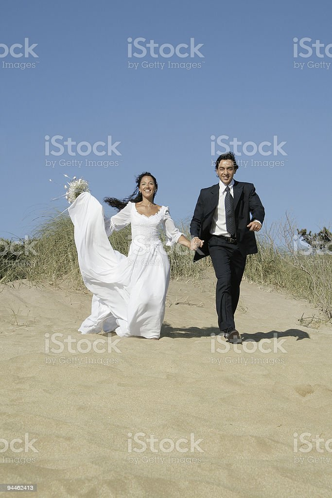 Bride and groom walking in the dunes royalty-free stock photo