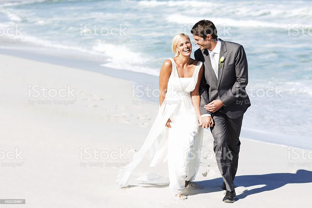 Bride And Groom Walking On Beach stock photo