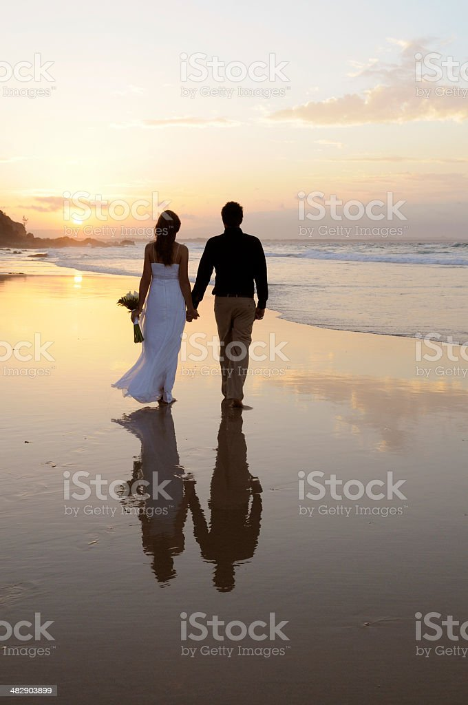 Bride and groom walking on the beach at sunset stock photo