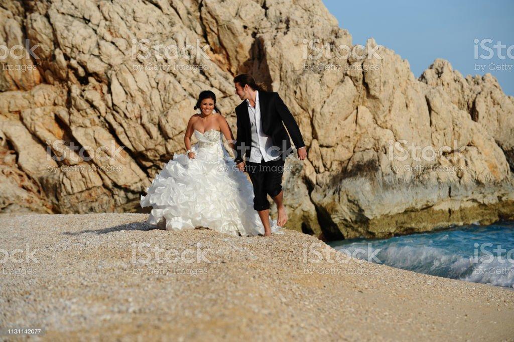 Gelin ve damat sahilde yürüyüş stok fotoğrafı