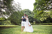 Japanese couple wearing wedding costumes relaxed in the park.